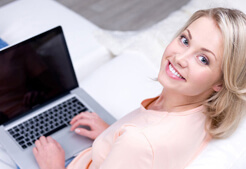 Pretty 2smiling woman using laptop Chicago Facelift Surgeon
